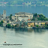 A boat sails out to an island in an Italian lake with castle and church near Milan