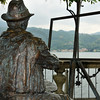 bronze statue of a painter wearing a hat, painting a lake and mountains