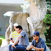 JMAG/T. Rob Brown<br /> Giao Nguyen, right, takes a break from the heat by relaxing with a Vietnamese beverage in the shade of a stone garden with his sons Bao Nguyen, 12, left, and Jon Nguyen, all of Denver, Colo., during Marian Days Thursday morning, Aug. 2, 2012, in Carthage.