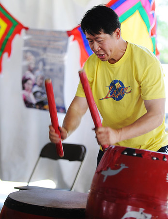 JMAG/T. Rob Brown<br /> Phong Nguyen, a parent with the La Salle Youth Group of San Jose, Calif., plays drums to help promote the youth group's stage performance during Marian Days Thursday morning, Aug. 2, 2012, in Carthage.