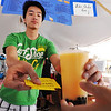 JMAG/T. Rob Brown<br /> Anh Bui, 20, of Our Lady of Vietnam in Amarillo, Texas, takes a customer's ticket as he hands them a cantaloupe variety of bubble tea during Thursday afternoon's heat, Aug. 2, 2012, at Marian Days in Carthage.