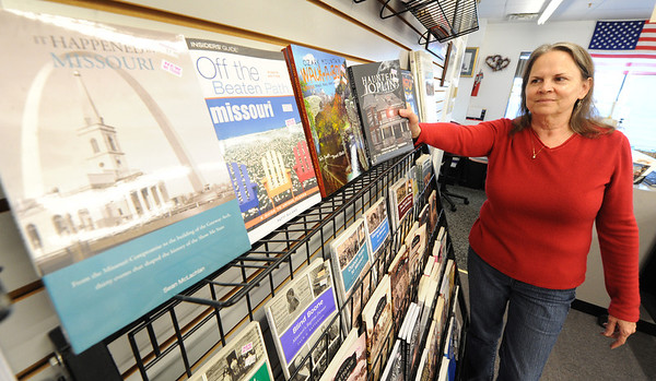 """JMag/T. Rob Brown<br /> Susie Davidson, owner of Changing Hands Book Shoppe, adds more copies of """"Haunted Joplin"""" to her local interest section. The store recently celebrated its 20th anniversary."""
