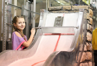 Bella Ballard of Wellington, age 11, demonstrates the toboggan run build by JVS students at the Lorain County Joint Vocational School open house in Oberlin. photo by Ray Riedel