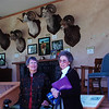 Anne and Marge Polson pose in front of the Leupold trailer displaying Jack O'Connor game heads. Marge was Dad's secretary.