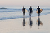 Three Surfers walking into the surf near the Jacksonville Beach, Florida Pier