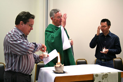Fr. Jack Kurps lights his candle while Fr. Cassidy blesses those gathered.