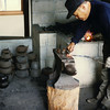 A smith makes handles for the pots and kettles. At the time I was surprised to see a Western-style anvil used, but I didn't have a good grip of how new integrated with tradition in Japanese crafts. But at any rate, the smith's posture looks back-crippling! His anvil should be much higher--knuckle height if he were standing erect.