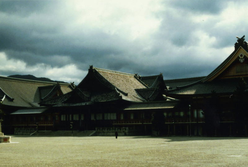 "So much for the real temples. Here we have the headquarters of the Tenri sect, a syncretic folk religion that arose after WWII. Located somewhere around Nara, the precincts are very large and spacious, and feature Soviet-style dorms for the visiting faithful. My notes from the pictures indicate ""the architecture is notable only for its scale...a mix of Shinto tradition, Buddhist influence, & concrete.""<br /> <br /> You can go in the main hall, but not up to the altar. Believers (BIG ones) are stationed everywhere and photos are forbidden. The remains of the founder, a woman, are kept in a special pit of some sort in the center of the main hall (you're not allowed to go near) and every day the priests go down and either offer her lunch, or eat lunch with her--it wasn't clear."
