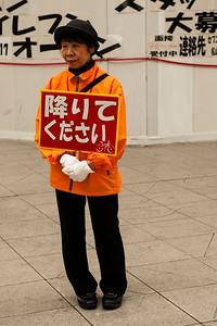 Les personnes agées au Japon effectuent souvent des petits jobs pour à la fois compléter leur retraite et garder une utilité sociale : ici cette dame rapellait l'interdiction aux bicyclettes de circuler dans la rue marchande et piétonne.