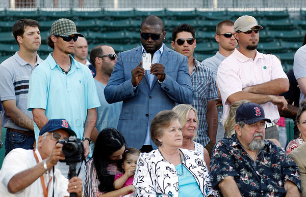 FORT MYERS, FL, March 1, 2012: Boston Red Sox designated hitter David Ortiz, center, records former teammate Jason Varitek's retirement announcement on his cellphone as, from left, other Red Sox players, standing from left, Rich Hill, Clay Buchholz, Dustin Pedroia, Jacoby Ellsbury, Michael Bowden and Josh Beckett listen. (Brita Meng Outzen/Boston Red Sox)
