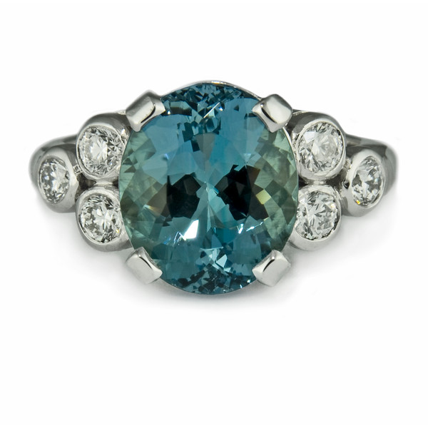 Aquamarine fleur-de-lis engagement ring<br /> <br /> Oval aquamarine with trefoil set shoulder diamonds set in platinum.<br /> <br /> Starting with just an idea about colour, Rumour Jewellery developed the design from the bottom up to be totally original.