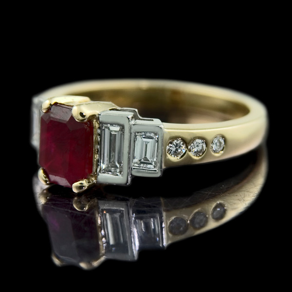 """Atlantic"" Emerald Cut Ruby Engagement Ring<br /> <br /> Emerald cut ruby ring with step-down diamond baguette shoulders on a brilliant cut diamond set shank. Set in platinum and 18ct yellow gold..<br /> <br /> Art Deco design lives on in this engagement ring created by and photographed for Rumour Jewellery"