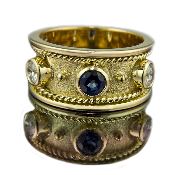 "Spin three<br /> <br /> ""Spin Three"" Eternity ring<br /> <br /> A round sapphire with two brilliant cut diamonds and alternate gold beads set in 18ct yellow gold.  Photographed for the website and portfolio.<br /> <br /> This is a variation on the Spin Six ring we made last year.<br /> <br /> My new photographic technique with a reflection on white seems to be working ok for this image."