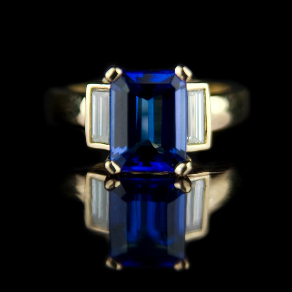 Emerald cut tanzanite engagement ring<br /> <br /> A more arty shot....2.33ct Tanzanite with 0.54cts of diamond baguette side stones in an 18ct yellow gold setting. <br /> <br /> Recently made for one of our clients and photographed for Rumour and our bespoke portfolio.