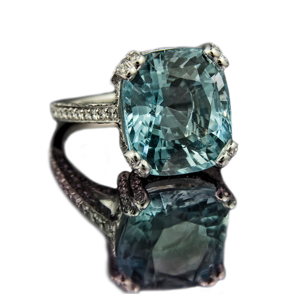 """Santa Maria"" Cushion cut aquamarine ring<br /> <br /> 9.8ct Cushion cut aquamarine with 1.60ct brilliant cut pave set diamonds.<br /> <br /> Perfect jewellery in this 18ct white gold engagement ring using a wonderful 14 x 12mm aquamarine and G/ VS diamonds<br /> <br /> Photographed for website and portfolio"