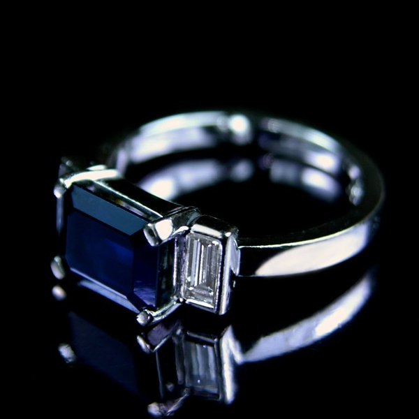 Emerald cut sapphire engagement ring<br /> <br /> I know that this doesn't show off the ring particuarly well .. but I liked the darkness of the central stone. Emerald cut sapphire and diamond engagement ring I photographed for our bespoke jewellery portfolio and website.