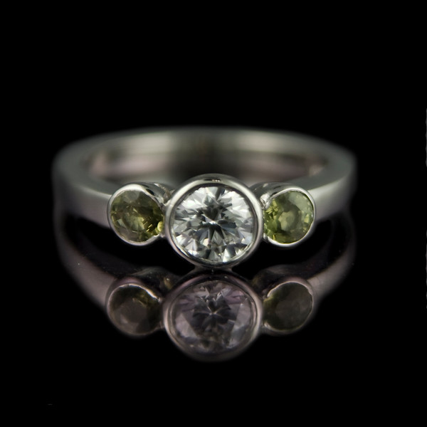 Green sapphire and diamond ring<br /> <br /> E colour VVs1 0.50ct brilliant cut diamond with two green sapphires set in platinum.<br /> Our use of the scalloped rub-over settings for the side stones works very well to create a smoother look to the overall design.<br /> <br /> A simple ring with unusual side stones makes this design a truly unique ring.  Photographed for our portfolio at Rumour Bespoke Jewellery.