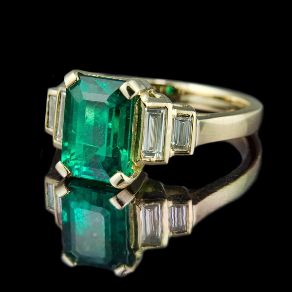 Emerald Cut Emerald Ring<br /> <br /> A yellow gold variation on this very nice classical design. 2.22ct Emerald cut emerald with double step-down 0.33ct baguette diamonds set in 18ct yellow gold.<br /> <br /> This engagement ring was handmade at the Rumour workshop in London