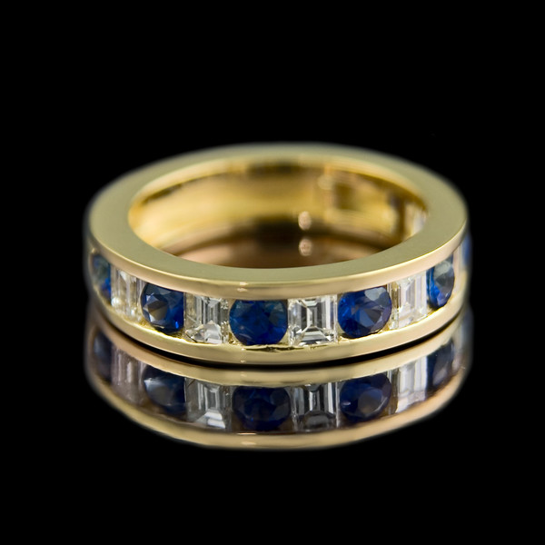 "Baguette and sapphire eternity<br /> <br /> Eternity Ring design ""Binary""<br /> <br /> 0.08ct baguette cut diamonds with alternate 0.14ct round sapphires channel set in 18ct yellow gold. This is a 3/4 eternity ring but can be 1/2 or full."