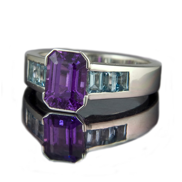 1.96ct Emerald cut purple sapphire in a rub-over setting and six 3 x 2mm channel set baguette aquamarine shoulders. Set in 18ct white gold.<br /> <br /> An unusual purple sapphire with a total of 0.61cts baguette cut aquamarines.  Photographed for Rumour Jewellery Bespoke portfolio