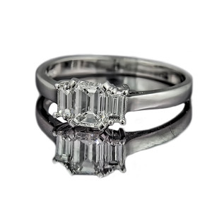A small deco-dence  Art Deco style emerald cut diamond engagement ring with step-down baguette diamonds set in platinum.  Central emerald cut diamond 0.84ct H colour, VS1 Clarity. Side baguette diamonds 0.12ct each