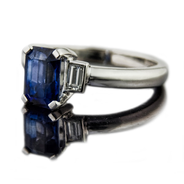 Emerald cut sapphire engagement ring<br /> <br /> Art-Deco style emerald cut sapphire with step-down baguette diamonds.  Well people are saying its like we are living in the 1930's!  2.55ct emerald cut blue sapphire set in 18ct white gold. The step-down baguette diamonds are 0.16cts each.<br /> <br /> I photographed this engagement ring for the  website portfolio.