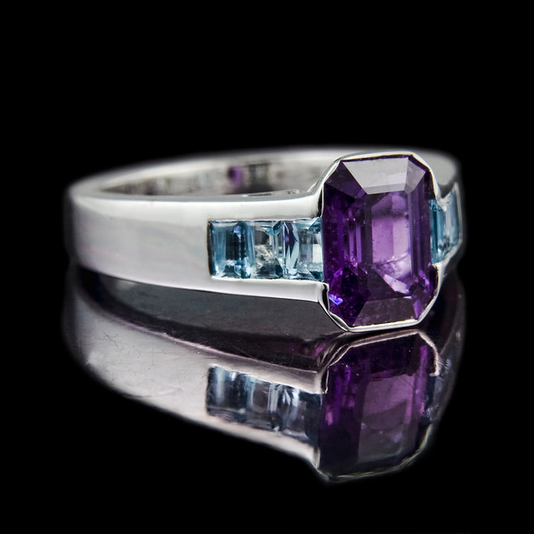 1.96ct Emerald cut purple sapphire in a rub-over setting and six 3 x 2mm channel set baguette aquamarine shoulders. Set in 18ct white gold.<br /> <br /> We had to remake this one as the client was not 100% happy.... now all stones reset in-line.<br /> <br /> An unusual purple sapphire with a total of 0.61cts baguette cut aquamarines. Photographed for Rumour Jewellery Bespoke portfolio