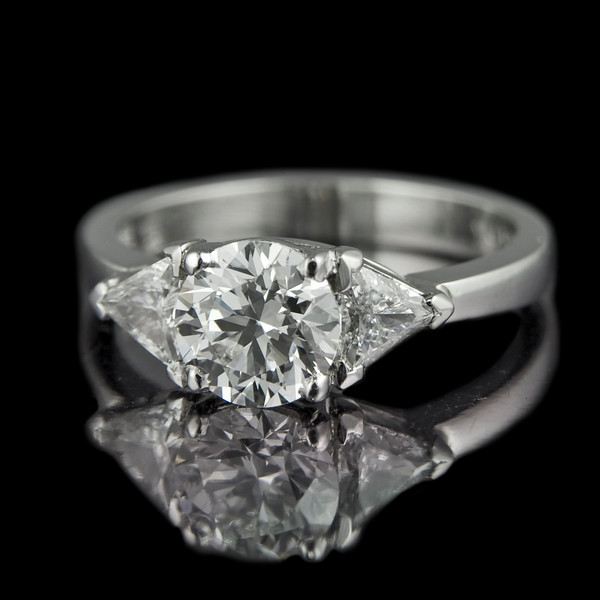 Brilliant-trillian diamond ring<br /> <br /> One of our old favourites...<br /> <br /> Brilliant cut diamond engagement ring with trillian side stones in a platinum setting..<br /> <br /> A classic Rumour ring design with beautiful complimentary shapes and symmetry.