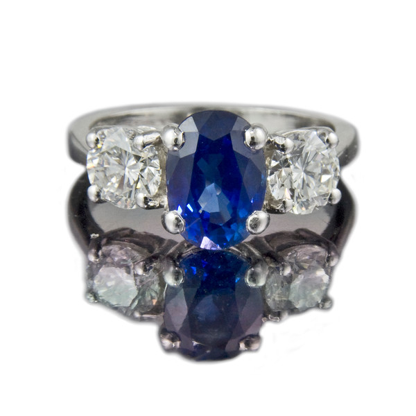 Cushion Cut Ceylon Sapphire Engagement Ring<br /> <br /> Four claw set cushion cut sapphire with a pair of 0.50ct brilliant cut diamond side stones in matching settings. Set in platinum.<br /> <br /> Similar to one of our other cushion cut sapphire designs, but, as ever, subtely different. This ring just came back for a tune-up and clean.