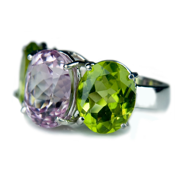 Kunzite and peridot cocktail ring (side)<br /> <br /> Kunzite (10x8mm) and peridot three stone cushion cut cocktail ring in 18ct white gold I photographed for our jewelery collection portfolio and website.<br /> <br /> Kunzite is the youngest member of the spodumene family  first studied in 1902 by gemmologist George Frederick Kunz. a delicate pink hue often displaying a hint of violet. The more intense the colour: the more valuable the stone.  Be careful sunbathing: the colour can fade in direct sunlight!