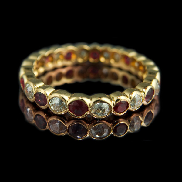 Ruby & diamond eternity ring<br /> <br /> Brilliant cut ruby and peridot eternity ring set in 18ct yellow gold..<br /> <br /> This full eternity ring combines a colourful style with minimalist design. Based on our diamond and ruby design.<br /> <br /> Photographed for Rumour Jewellery website and portfolio