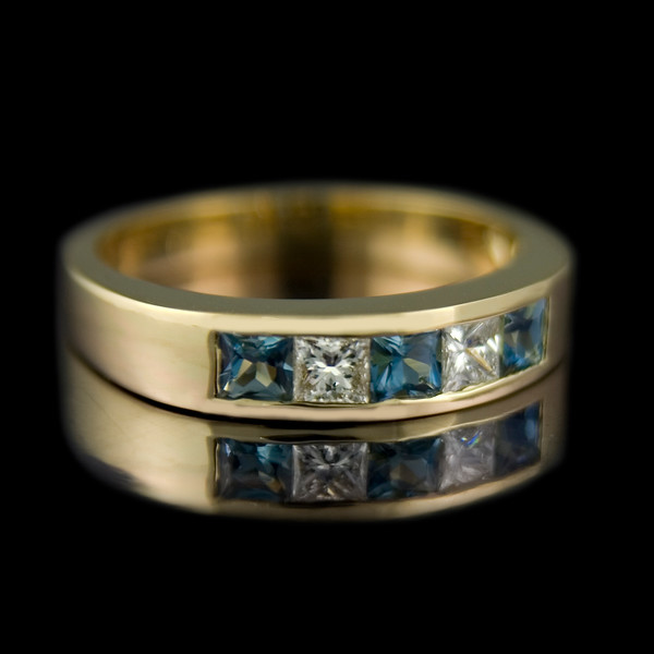 Aquamarine and diamond eternity ring<br /> <br /> Channel set 3mm x 3mm princess cut diamond and aquamarine half eternity ring in a 18ct yellow gold setting.<br /> <br /> Made for one of our clients.