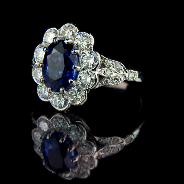 Oval sapphire with diamond cluster engagement ring<br /> <br /> A bespoke engagement ring I photographed for our jewellery portfolio and website. This is the white background version