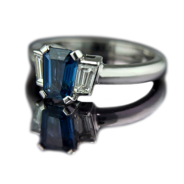 """Empire"" Art Deco Sapphire engagement ring<br /> <br /> Art Deco for the 21st century.<br /> <br /> A specially cut 1.85ct sapphire and 0.60cts diamond ring set in 18ct white gold<br /> <br /> This ring was designed to match the glamour of the Art Deco era that it was inspired by, but with state-of-the-art computer aided design to make sure the stones were cut exactly.<br /> <br /> Photographed for Rumour Jewellery website and portfolio."
