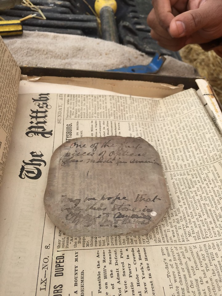 """This is a piece of optical glass with an inscription that reads """"One of the first pieces of optical Glass Made in America"""".  """"May we hope that when this ---? stone is opened for America""""(s) use in this land......  (?)"""