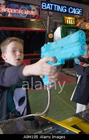 TA17.17 m580 / Choice 4 of 7 / A9M195 Boy playing video game with toy gun in arcade