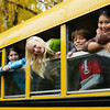 TA16.1 m517 / Choice 5 of 10 / Group of young students hanging out windows of school bus smiling