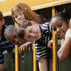 TA16.1 m517 / Choice 8 of 10 / Portrait of children looking out of a school bus