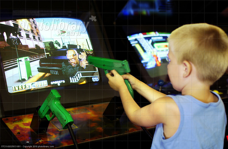 TA17.17 m580 / Choice 2 of 7 / Young boy aiming toy gun at arcade game screen