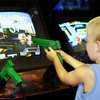 TA17.17 m580 / Choice 2 of 7 / Young boy aiming toy gun at arcade game screen