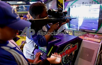 TA17.17 m580 / Choice 3 of 7 / In this photo taken Sept. 2, 2009, a boy, using a toy weapon, plays a video game in Caracas. Venezuela's National Assembly is on track to prohibit violent video games and toys. The proposed legislation, which received initial approval in September, is expected to get a final vote in the coming weeks. (AP Photo/Ariana Cubillos)