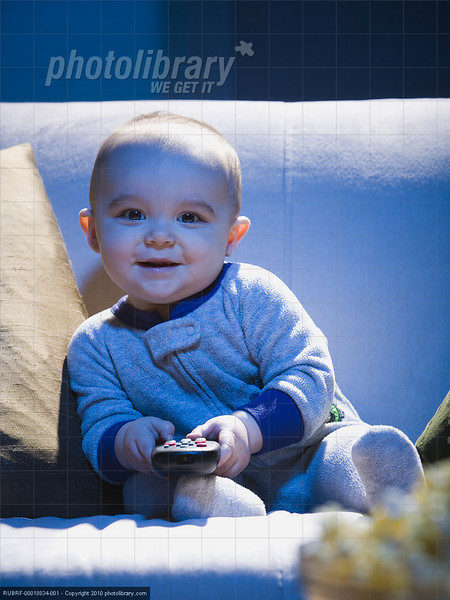 TA17.18 m581 / Choice 7 of 7 / Baby on sofa with television remote smiling