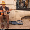 An elderly bearded man busker playing his guitar busking in Norwich , Norfolk , Uk