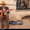 An elderly bearded man busker playing his guitar busking in Norwich , Norfolk , Uk