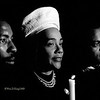 """Give Peace a Chance"", 	This documentary portrait of Coretta Scott King was photographed in 1968 during a candle light procession in Memory of her late husband Martin Luther King Jr. Walter Fauntroy then Mayor of the District of Columbia accompanies Coretta Scott King on the right, and Stony Cooks on the left from Union, Alabama. Approximately 100,000 people peacefully marched in the candle light procession from the Washington Monument to the White House lead by Coretta Scott King. The digitally enhanced photographic print was traditionally photographed, using street lamp and candle light illumination, with a Nikon FTN camera on Ilford FP4 black and white 35mm negative film rated at ISO 1200 and processed in Acufine developer stock solution for ten minutes."