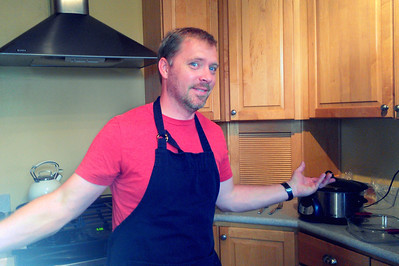 Bryan in his new kitchen, fixing enchiladas with mole.
