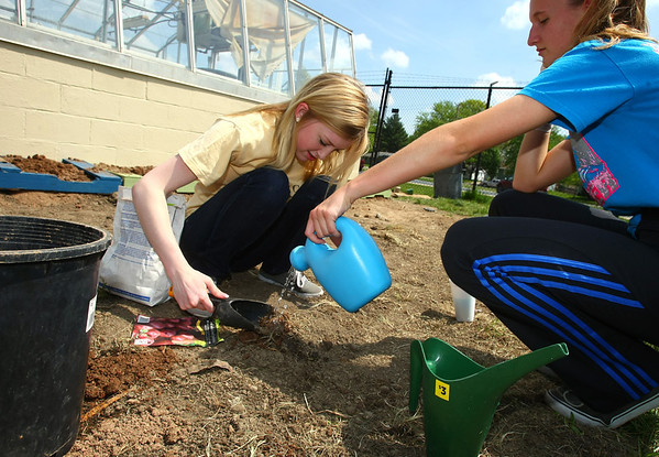 5-8-13<br /> Kokomo Area Career Center culinary arts students planting an herb and vegetable garden at KHS.<br /> Kristen Mettin and Amanda Kuffell plant potatoes.<br /> KT photo | Tim Bath