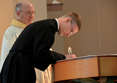 Signing his vows with Fr. Steve looking on