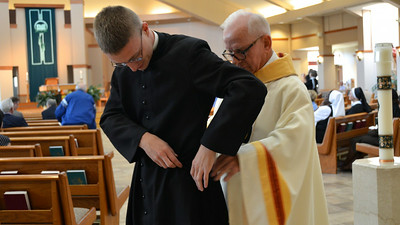 Fr. John, Justin's novice master, helps Justin with his cord.