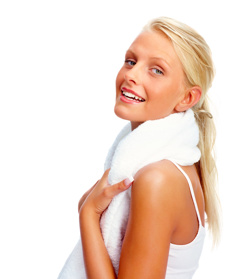 Attractive young female with a towel around her neck smiling over white background